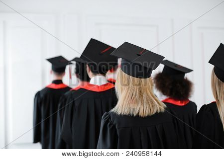 Students in bachelor robes and mortarboards indoors. Graduation day