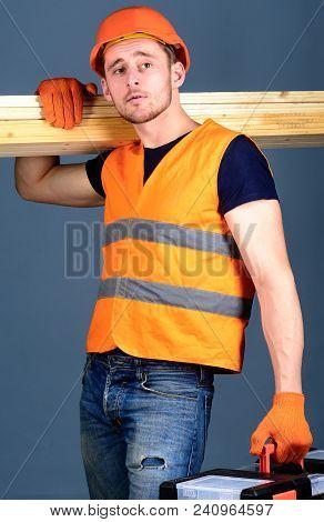 Carpenter, Woodworker, Labourer, Builder On Calm Face Carries Wooden Beams On Shoulder. Man In Helme