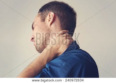 Businessman Holding A Phone And Her Neck With Pain. Young Guy Holding His Neck. A Sore Neck. Chondro
