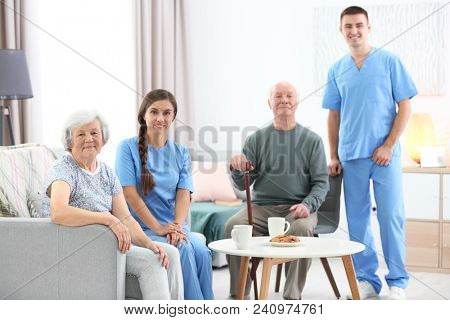 Senior man and woman with their caregivers indoors