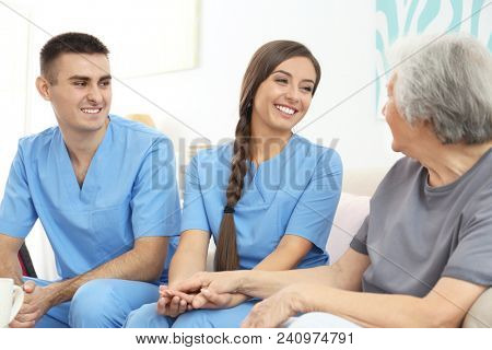 Senior woman with young caregivers indoors