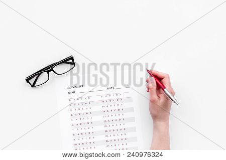 Take The Exam, Write The Exam. Hand With Pen Near Exam Paper On White Background Top View.