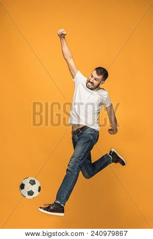 The Young Man As Soccer Football Player Jumping And Kicking The Ball At Studio On A Yellow Backgroun