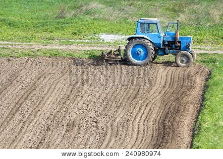 Blue Dusty Tractor With Seedbed Cultivator Standing At The Edge Of Freshly Plowed And Cultivated Fie