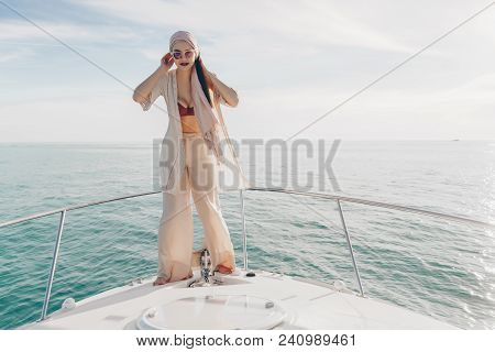 Elegant Stylish Girl In Sunglasses Posing On A White Yacht, Went On A Sea Voyage