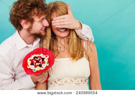 Handsome Man Giving Woman Candy Bunch Flowers. Young Boyfriend With Surprise Present Gift For Girlfr