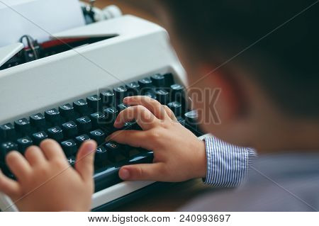 Close-up Of Hand Of Boy As Business Executive Using Typewriter.