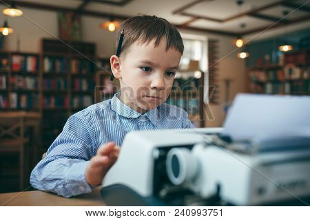 Side View,  Preschool Journalist Boy Sitting At Table And Typing Typewriter With  A Pencil On The To