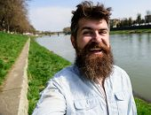 Man, tourist with beard and mustache on cheerful, smiling face, riverside background. Selfie photo concept. Hipster, tourist with tousled hair and long beard looking at camera, taking selfie photo. poster