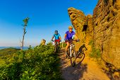 Cycling women and man riding on bikes at sunset mountains forest landscape. Couple cycling MTB enduro flow trail track. Outdoor sport activity. poster