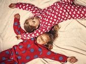 Girls in pajamas sleep in bed, top view. Good night, napping, bedtime, slumber, dream sleepover concept poster