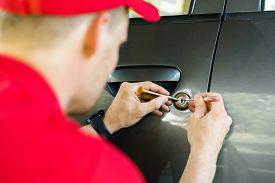 Locksmith In Red Uniform Opening Car Door With Lockpicker