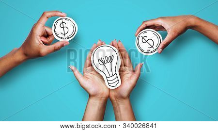 Money For Startup, Startup Financing. Hands With Dollar Sign Coins And Light Bulb Over Blue Backgrou