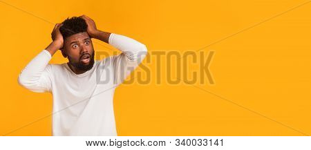 Shocked African American Guy With Open Mouth Touching His Head And Looking At Copy Space, Seeing Sho