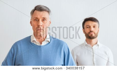 Serious Senior Man And His Middle Aged Son Standing Looking At Camera Against White Wall. Panorama,