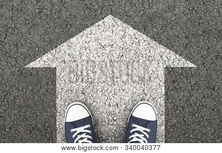Just Move On, Keep Going. Blue Sneakers On The Asphalt Road With Drawn Arrow. Top View,