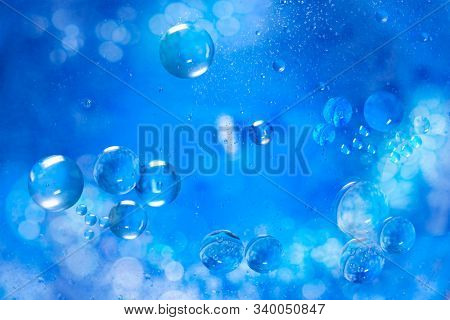 Small air bubbles in sea water. Macro photo. Blue abstract background. Illuminated liquid surface.