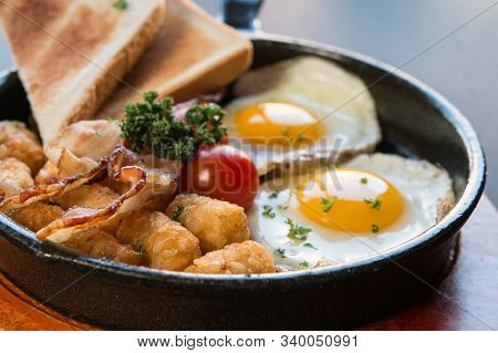 Scrambled Egg Skillet With Toast,hash Brown,tomatoes On A Black Background And Wooden Plate,