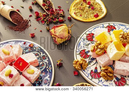 Eastern sweets. Traditional Turkish delight Rahat lukum with rose and citrus on ceramics with typical folk patterns. Fruit sugar, sumac in wooden shovels. Sun rays stone background close up poster