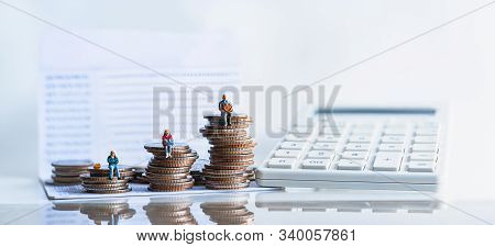Miniature People: Elderly People Sitting On Coins Stack. Pensions And Retirement Planning. Money Sav