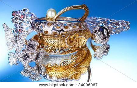 Beautiful silver and gold bracelets and rings on blue background
