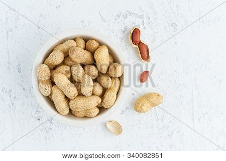 Top View Plate With Peanut In Endocarp, Bowl With Drupe In Shell On A White Table. Stone Background,