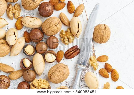 Mix Of Nuts - Walnut, Almonds, Pecans, Macadamia And Knife For Opening Shell On White Wooden Cutting