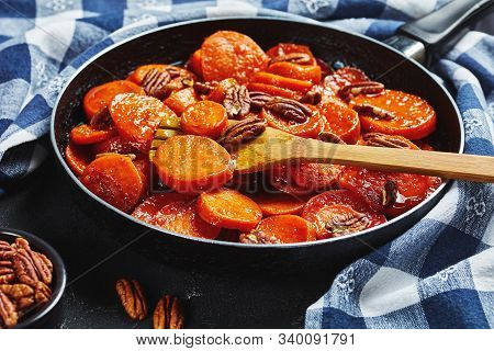 Close-up Of Candied Sweet Potatoes With Brown Sugar, Maple Syrup, Orange Juice And Pecan Nuts In A S