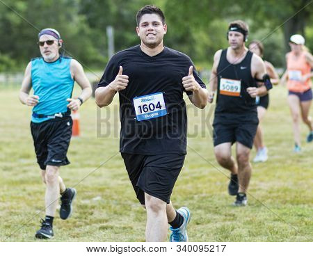 Kings Park, New York, Usa - 17 June 2019: A Young Male Runner Giver Two Thumbs Up Toward The Camera