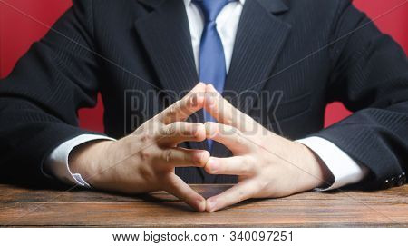 A Man Sits With His Hands In The Lock. Conflict Resolution, Search For A Compromise. Pondering A Pro
