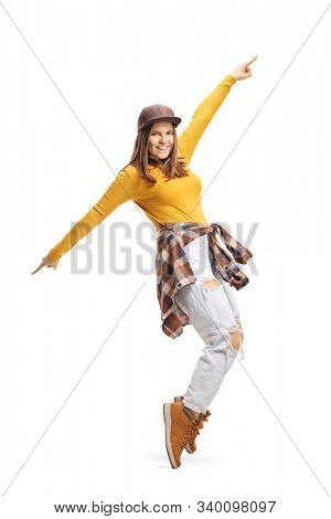 Full length shot of a young woman in casual clothes dancing on tiptoes isolated on white background