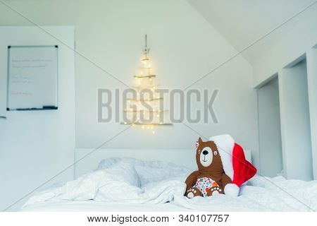 Cozy Toy Bear In Santa Hat Sitting On The Bed On Background Of Unusual Christmas Tree Made Of Wooden