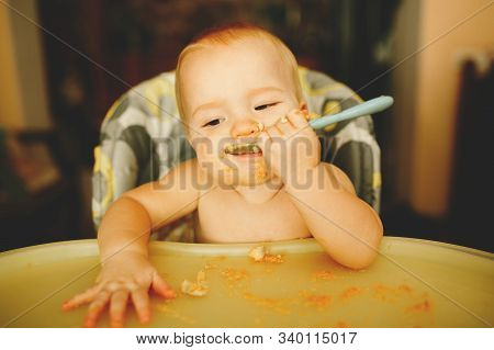 Beautiful Blond Boy Eats Porridge And Laughs