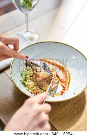 Lunch In A Restaurant, A Woman Cuts Delicious Duck Leg Su-vide, With Bulgur And Onion Marmalade. Bar