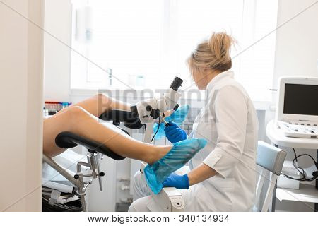 A Blond Woman Doctor, Gynecologist Examines A Patient Who Is Sitting In A Gynecological Chair. Exami