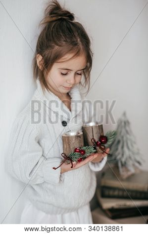 Stock Photo -  Beautiful Little Girl With Wooden Christmas Decor In Hands