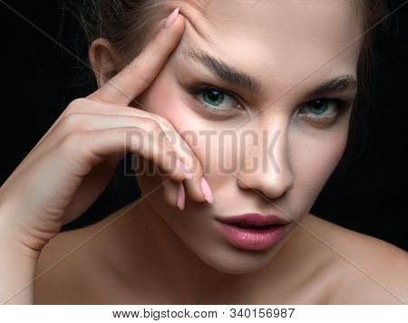 Close Up Portrait Of A Beautiful Woman Toucnig Her Eyebrow Over Dark Background. Beauty And Cosmetol