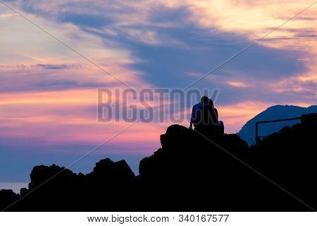 Loving Couple On Rocks Observing Pink Sunset
