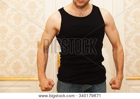Young aggressive Caucasian man in black shirt clenches his fists menacingly, domestic violence concept poster