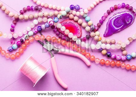 Colored Stone Beads And Agate Druses For Jewelry Making On Pink Background. Hobby, Handmade, Fine Ar