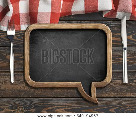 menu blackboard frame on old wooden dinning table with red tablecloth, tableknife and fork
