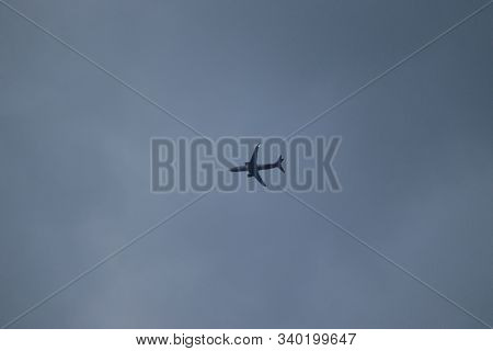 White Passenger Airplane In The Clouds At Sunset.commercial Airplane Jetliner Flying Above Dramatic