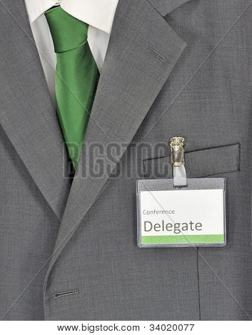 Male gray business suit green tie and conference badge