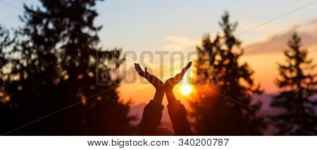 Sun In Hands. Sunset On The Background Of Raised Hands.