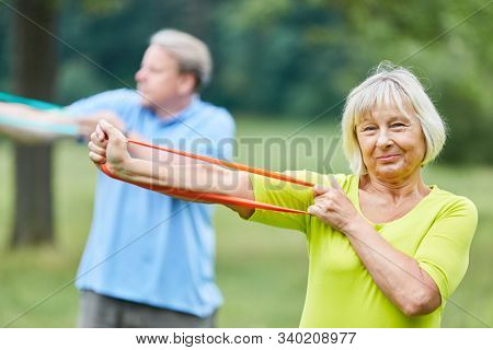 Senior couple in rehab exercising with the fitness band or elastic band