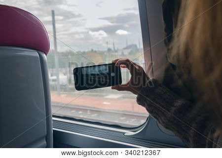 Woman Photographing With Cellphone Through Window While Traveling By Train. Young Traveler Woman In