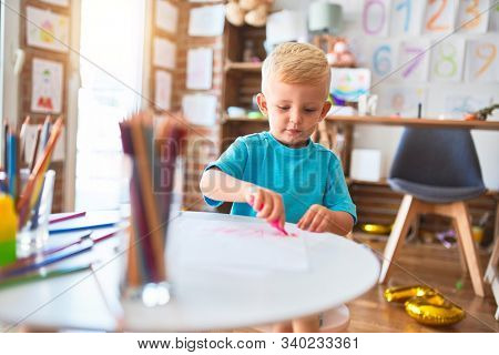 Young caucasian kid playing at kindergarten drawing with color pencils. Preschooler boy happy at playroom.