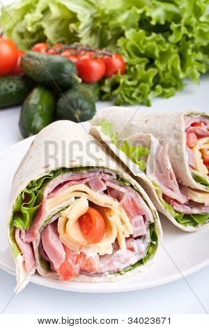 wrapped tortilla sandwich rolls cut in half with ingredients
