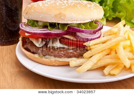 cheeseburger, french fries and cola on a wooden table