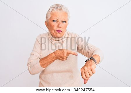 Senior grey-haired woman wearing turtleneck sweater standing over isolated white background In hurry pointing to watch time, impatience, upset and angry for deadline delay